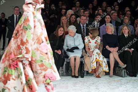 Queen Elizabeth II sits with Anna Wintour (third left), Caroline Rush (left), chief executive of the British Fashion Council (BFC) and royal dressmaker Angela Kelly (fourth left), as they view Richard Quinn's runway show before presenting him with the inaugural Queen Elizabeth II Award for British Design as she visits London Fashion Week's BFC Show Space in central London.
