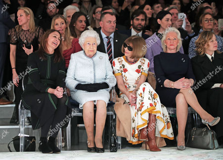 Queen Elizabeth II sits with Anna Wintour (third right) and Caroline Rush, chief executive of the British Fashion Council (BFC) (left) and royal dressmaker Angela Kelly (second right), as they view Richard Quinn's runway show before presenting him with the inaugural Queen Elizabeth II Award for British Design as she visits London Fashion Week's BFC Show Space in central London.