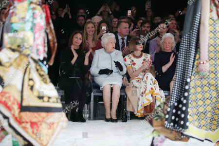 Queen Elizabeth II reacts as she sits with Anna Wintour (second right) and Caroline Rush (left), chief executive of the British Fashion Council (BFC) and royal dressmaker Angela Kelly (right), as they view Richard Quinn's runway show before presenting him with the inaugural Queen Elizabeth II Award for British Design as she visits London Fashion Week's BFC Show Space in central London.