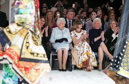 Queen Elizabeth II reacts as she sits with Anna Wintour (third right) and Caroline Rush (left), chief executive of the British Fashion Council (BFC) and royal dressmaker Angela Kelly (second right), as they view Richard Quinn's runway show before presenting him with the inaugural Queen Elizabeth II Award for British Design as she visits London Fashion Week's BFC Show Space in central London.