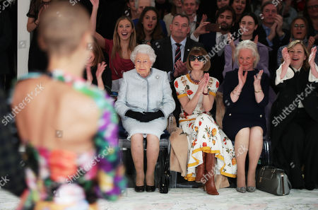 Queen Elizabeth II sits with Anna Wintour (third right) and Caroline Rush, chief executive of the British Fashion Council (BFC) (partially hidden left) and royal dressmaker Angela Kelly (second right), as they view Richard Quinn's runway show before presenting him with the inaugural Queen Elizabeth II Award for British Design as she visits London Fashion Week's BFC Show Space in central London.