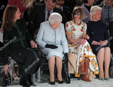 Queen Elizabeth II sits with Anna Wintour (second right), Caroline Rush (left), chief executive of the British Fashion Council (BFC) and royal dressmaker Angela Kelly (right), as they view Richard Quinn's runway show before presenting him with the inaugural Queen Elizabeth II Award for British Design as she visits London Fashion Week's BFC Show Space in central London.