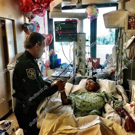 This image made available by the Broward County Sheriff's Office, shows Sheriff Scott Israel, holding the hand of Anthony Borges, 15, a student at Marjory Stoneman Douglas High School. The teenager was shot five times during the massacre on Valentine's Day that killed 17 students. Borges is being credited with saving the lives of at least 20 other students