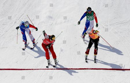 From left Francois Place, of France, Russian athlete Sergey Ridzik Jean Frederic Chapuis, of France, and Dave Duncan, of Canada, finish during the men's ski cross quarterfinal at Phoenix Snow Park at the 2018 Winter Olympics in Pyeongchang, South Korea