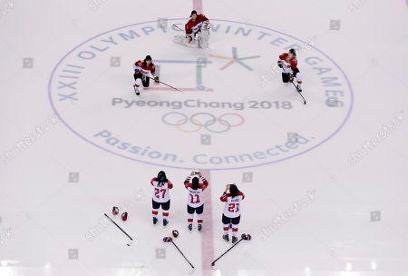 Tomomi Iwahara (22), Nana Fujimoto (1), and Ami Nakamura (23), of Japan, pose for photos by teammates Shoko Ono (27), Yurie Adachi (11) and Hanae Kubo (21) at the Kwandong Hockey Centre during the 2018 Winter Olympics in Gangneung, South Korea