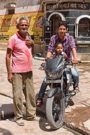 Man and child on motorcycle with older man, Bera, Rajasthan, India