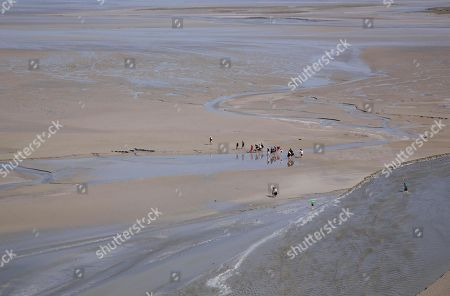 Hikers in mudflat at low tide in Mont Saint Michel, Normandy, France