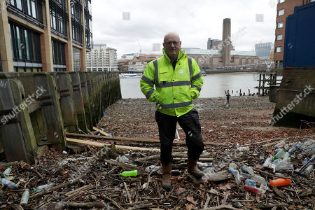 Volunteer Michael Byrne poses for photographs beside plastic bottles washed up on the foreshore at the site of the ancient and no-longer used Queenhithe dock, a designated scheduled monument which dates back to at least the time of King Alfred the Great who lived from 849 to 899 AD, on the north bank of the River Thames in London, . Amid growing evidence of dire amounts of waste in the world's oceans, conservation is becoming a selling point for firms trying to jump on the bandwagon of concern about the flood of plastic choking sea life