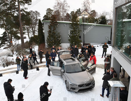 Journalists and reporters stand around the Swedish Volvo carmaker's new 'V60' station wagon model that was presented by Volvo Cars CEO Hakan Samuelsson (unseen) during an outdoor press meeting outside of Stockholm, Sweden, 21 February 2018.