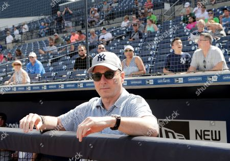 New York Yankees General Manager Brian Cashman looks out from the dugout at baseball spring training camp, in Tampa, Fla