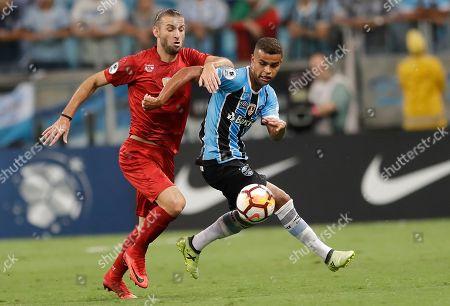 Alisson of Brazil's Gremio, right, fights for the ball with Gaston Silva of Argentina's Independiente during a Recopa Sudamericana final soccer match, in Porto Alegre, Brazil