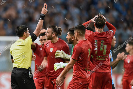 Referee Enrique Caceres, left, shows a red card to Fernando Amorebieta of Argentina's Independiente, holding his head at right, during the Recopa Sudamericana final soccer match with Brazil's Gremio in Porto Alegre, Brazil