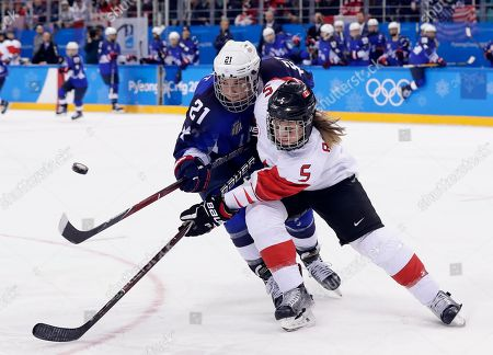 Lauriane Rougeau (5), of Canada, and Hilary Knight (21), of the United States, battle for the puck during the second period of the women's gold medal hockey game at the 2018 Winter Olympics in Gangneung, South Korea