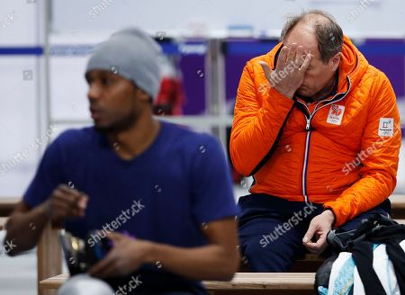 Coach Jac Orie of The Netherlands rubs his head as he sits behind Shani Davis of the U.S., left, after a practice session for the men's 1,000 meters speedskating race at the Gangneung Oval at the 2018 Winter Olympics in Gangneung, South Korea