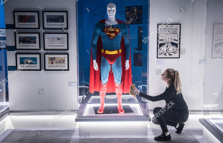 A woman cleaning the display case of the Superman Outfit worn by Christopher Reeve