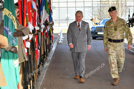 Stock Image of Prince Charles walks past flags representing NATO countries as he arrives, accompanied by Commander Allied Rapid reaction Corps Lieutenant General Tim Radford CB DSO OBE, during a visit to the headquarters of the Allied Rapid Reaction Corps