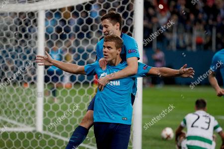 Zenit's Aleksandr Kokorin, bottom, celebrates scoring his side's third goal during the Europa League round of 32 second leg soccer match between Zenit St. Petersburg and Celtic at the Saint Petersburg stadium, in St. Petersburg, Russia