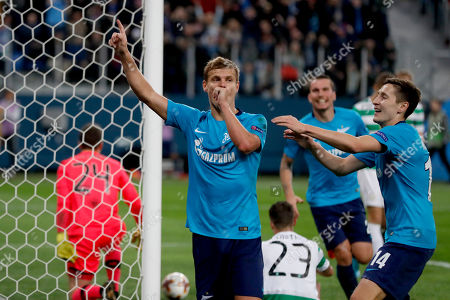 Zenit's Aleksandr Kokorin, left, celebrates scoring his side's third goal during the Europa League round of 32 second leg soccer match between Zenit St. Petersburg and Celtic at the Saint Petersburg stadium, in St. Petersburg, Russia