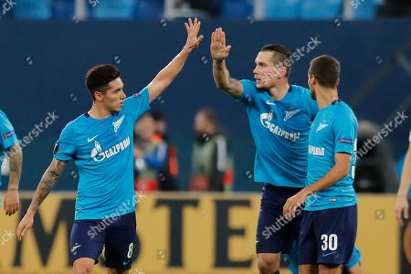 Zenit's Daler Kuzyayev, second right, celebrates scoring his side's second goal during the Europa League round of 32 second leg soccer match between Zenit St. Petersburg and Celtic at the Saint Petersburg stadium, in St. Petersburg, Russia