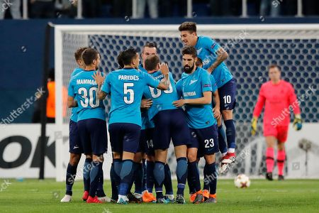 Zenit players surround and celebrate with Daler Kuzyayev, obscured, after he scored his side's second goal during the Europa League round of 32 second leg soccer match between Zenit St. Petersburg and Celtic at the Saint Petersburg stadium, in St. Petersburg, Russia