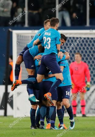 Zenit players jump and celebrate with Daler Kuzyayev, obscured 14, after he scored his side's second goal during the Europa League round of 32 second leg soccer match between Zenit St. Petersburg and Celtic at the Saint Petersburg stadium, in St. Petersburg, Russia