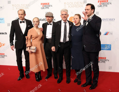 Stock Photo of Author Heinz Strunk (3-R) and actor Charly Huebner (R) pose with cast members of 'Juergen - Heute wird gelebt' as they arrive for the 53rd annual 'Goldene Kamera' (Golden Camera) film and television award ceremony in Hamburg, Germany, 22 February 2018.