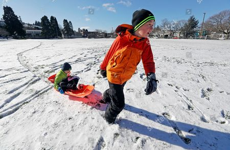 Cameron Moore, 12, pulls his brother Lucas, 8, along on a sled across a play field covered with about an inch of snow Thursday morning, in Seattle. Black ice and snow covered most roadways as a cold winter storm held the Pacific Northwest in its grips. Cold temperatures left a layer of ice on roads and sidewalks