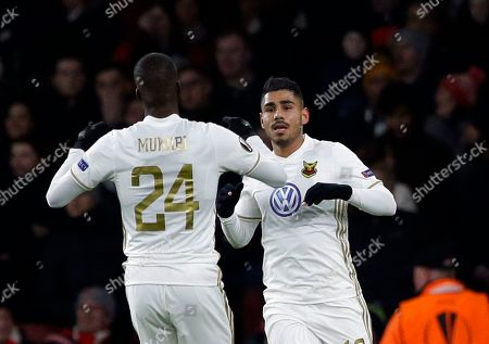 Ostersunds' Hosam Aiesh, celebrates with teammate Ronald Mukiibi after the own goal by Arsenal's Calum Chambers during the Europa League Round of 32, second leg soccer match between Arsenal and Ostersunds FK at the Emirates Stadium in London