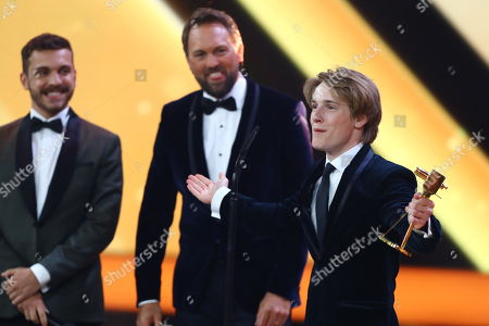 Actor Louis Hofmann (R) receives the newcomer awards from Edin Hasanovic (L) and Steven Gaetjen during the 53rd annual 'Goldene Kamera' (Golden Camera) film and television award ceremony in Hamburg, Germany, 22 February 2018. Liam Neeson was awarded for his lifetime achievement.