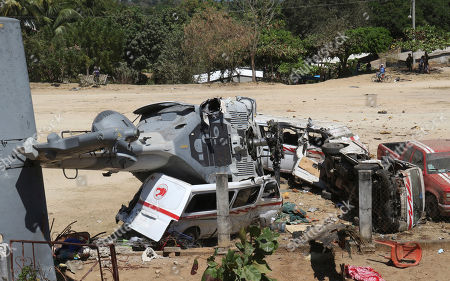 A downed helicopter sits on its side on top of a van, in Santiago Jimitepec, Oaxaca state, Mexico. The military helicopter carrying officials assessing earthquake damage crashed killing 13 people and injuring 15, all of them on the ground