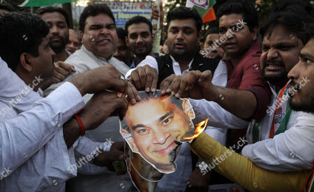 Indian Youth Congress activists burns the mask of billionaire jeweler Nirav Modi and shout slogans against the government during a protest against Bhartiya Janta Party (BJP) led government in Mumbai, India, 23 February 2018. According to a news report, activists protested against the fraud sceme allegedly orchastrated by Nirav Modi, worth 1.77 billion US dollar at India's second-biggest state-run bank Punjab National Bank (PNB) branch in Mumbai, blaming the Indian government for their alleged involvement.