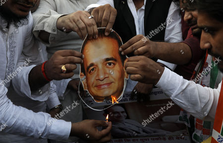 Indian Youth Congress activists burn the mask of billionaire jeweler Nirav Modi and shout slogans against the government during a protest against Bhartiya Janta Party (BJP) led government in Mumbai, India, 23 February 2018. According to a news report, activists protested against the fraud sceme allegedly orchastrated by Nirav Modi, worth 1.77 billion US dollar at India's second-biggest state-run bank Punjab National Bank (PNB) branch in Mumbai, blaming the Indian government for their alleged involvement.