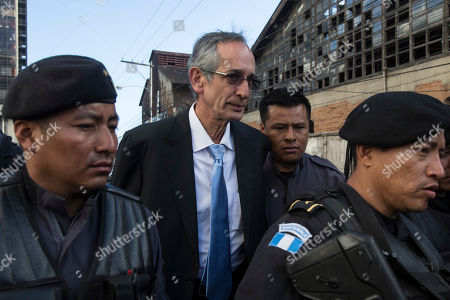 Former Guatemalan President Alvaro Colom is escorted by police as he arrives at a courthouse for his first hearing, in Guatemala City, . Colom is involved in a fraud and embezzlement case against him and nearly his entire former cabinet