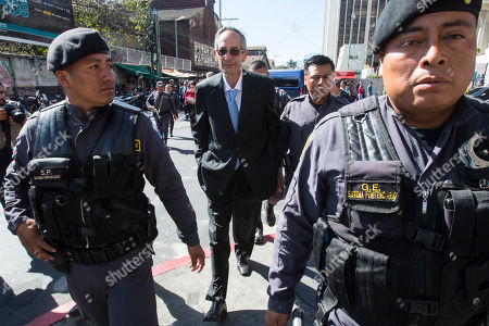 Former Guatemalan President Alvaro Colom, center, walks to a courtroom escorted by police, for his first hearing, in Guatemala City, . Colom is involved in a fraud and embezzlement case against him and nearly his entire former cabinet