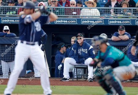 San Diego Padres bench coach Mark McGwire, center, watches from the dugout during the second inning of a spring training baseball game against the Seattle Mariners, in Peoria, Ariz