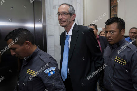 Former Guatemalan President Alvaro Colom is escorted by police before his first hearing at a courtroom, in Guatemala City, . Colom is involved in a fraud and embezzlement case against him and nearly his entire former cabinet