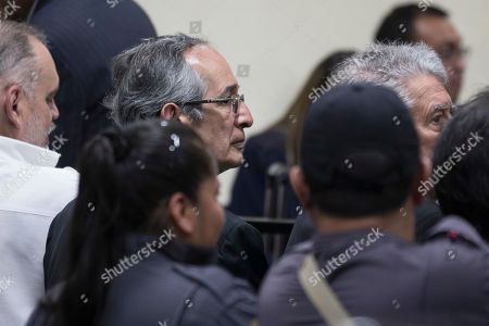 Former Guatemalan President Alvaro Colom, center, sits in a courtroom for his first hearing, in Guatemala City, . Colom is involved in a fraud and embezzlement case against him and nearly his entire former cabinet