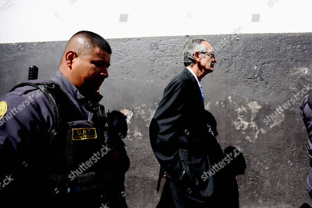 The Former President of Guatemala Alvaro Colom (R)(2008-2012) walks with prison system guards, in Guatemala City, Guatemala, 23 February. 2018. The Guatemalan Prosecutor's Office filed fraud and embezzlement  charges against  twelve former officials of the Colom government (2008-2012), including the former President and former finance minister who is now Oxfam International Chairman Juan Alberto Fuentes Knight, in connection to a corruption scheme in public transport.