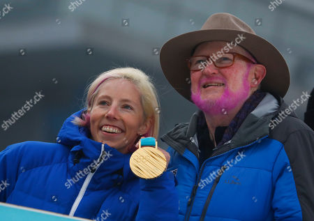 Tom Kelly, right, vice president of communications for the United States Ski and Snowboarding team and Kikkan Randall pose foe a picture during men's 50k cross-country skiing competition at the 2018 Winter Olympics in Pyeongchang, South Korea, . Tom Kelly, made good on a 12-year-old promise to American cross-country skier Kikkan Randall to dye his hair pink if she ever won an Olympic medal