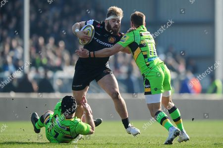 Luke Cowan-Dickie of Exeter Chiefs is tackled by Heinrich Brussow of Northampton Saints and Ben Foden of Northampton Saints during the Aviva Premiership match between Exeter Chiefs and Northampton Saints at Sandy Park on February 24th 2018, Exeter, Devon (