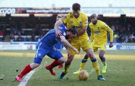 Jack Marriott of Peterborough United tangles with Jonathan Meades of AFC Wimbledon
