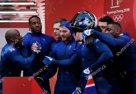 Driver Brad Hall, Greg Cackett, Nick Gleeson and Joel Fearon of Britain and Driver Lamin Deen, Andrew Matthews, Toby Olubi and Ben Simons of Britain congratulate each other after they finished their final heat during the four-man bobsled competition final at the 2018 Winter Olympics in Pyeongchang, South Korea