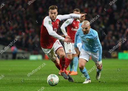 Manchester City's David Silva holds off the challenge from Arsenal's Calum Chambers to score