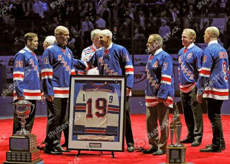 Mark Richter, Mark Messier, Jean Ratelle, Rod Gilberrt, Brian Leetch, Adam Graves. Retired New York Rangers player Mark Richter, far left, watches as Mark Messier, second from left, as he greets Hockey Hall of Famer Jean Ratelle, wearing a number 19 jersey, in front of Ratelle's framed playing jersey during a ceremony retiring Ratelle's number before an NHL hockey game between the New York Rangers and Detroit Red Wings at Madison Square Garden in New York, . Ratelle, who played parts of 16 of his 21 NHL seasons with the Rangers, entered the Hockey Hall of Fame in 1985 and is second on the Rangers' goals list with 336 and third in assists with 481 and points with 817. Other Rangers who've had their numbers retired are at right, Rod Gilbert, Brian Leetch, Adam Graves