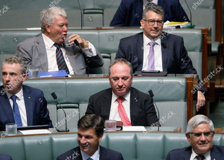 Former Australian Nationals party leader and Deputy Prime Minister Barnaby Joyce, center, looks down while sitting in parliament in Canberra, . Joyce quit as party leader and deputy prime minister over a sexual harassment allegation