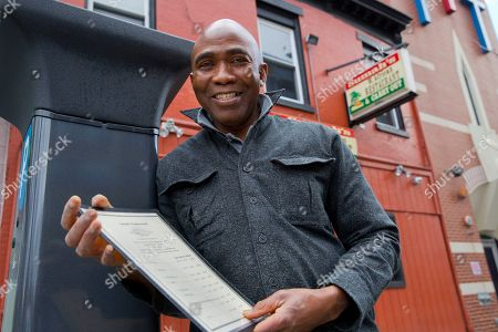Stock Photo of Amara Sumah, owner of Sumah's West African Restaurant, poses while holding one of the restaurant's menus, in the Shaw neighborhood of Washington. Twenty-five years ago, Sumah and his wife, Isata, immigrated from Sierra Leone and arrived in the U.S. as penniless college students. They have a classic American story, with a home in nearby suburbs, and a successful family-owned business that helps pay for their children's college education