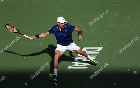 Florian Mayer of Germany returns the ball to Roberto Batista Agut of Spain during the Dubai Duty Free Tennis Championship in Dubai, United Arab Emirates
