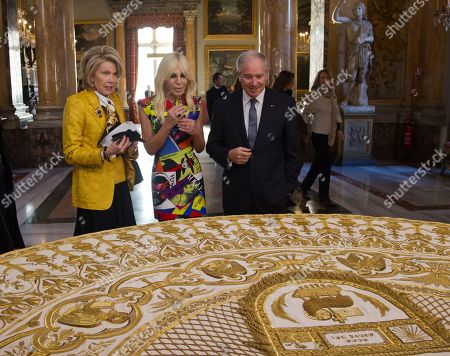 "From left, Christine Hearst Schwarzman, Donatella Versace and Stephen A. Schwarzman, CEO of Blackstone, look at a liturgical vestment of pope Benedict XV, in Rome, . The Vatican culture minister, Cardinal Gianfranco Ravasi, joined Vogue Editor-in-Chief Anna Wintour and designer Donatella Versace in Rome on Monday to display a few of the Vatican treasures at the Palazzo Colonna, a onetime papal residence. ""Heavenly Bodies: Fashion and the Catholic Imagination"" is set to open May 10 at the Met's Costume Institute in New York"