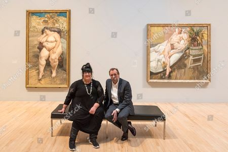 Sue Tilley and David Dawson sit with paintings of themselves by Lucian Freud (L to R) 'Sleeping by the Lion Carpet', 1996, and 'David and Eli', 2003-4.
