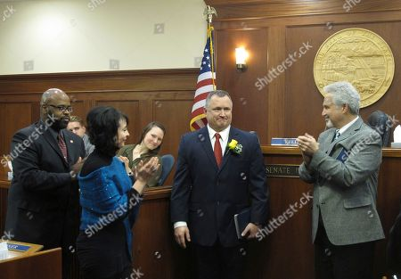 Alaska Sen. Mike Shower of Wasilla, second from right, receives applauses after being sworn in as a state senator, in Juneau, Alaska. Also shown standing are, from left, state Sens. David Wilson of Wasilla, Shelley Hughes of Palmer and Pete Kelly, the Senate president